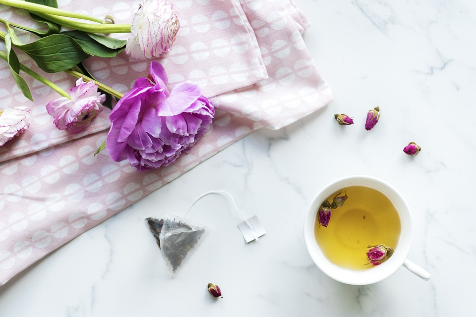 a cupy of herbal tea next to a rose