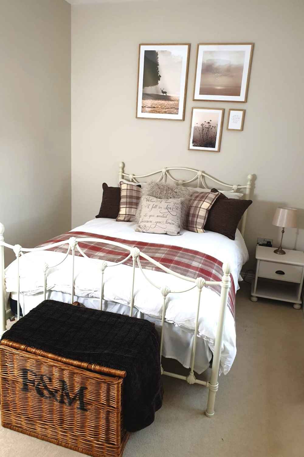 a bedroom with pictures on the wall and a basket at the foot of the bed