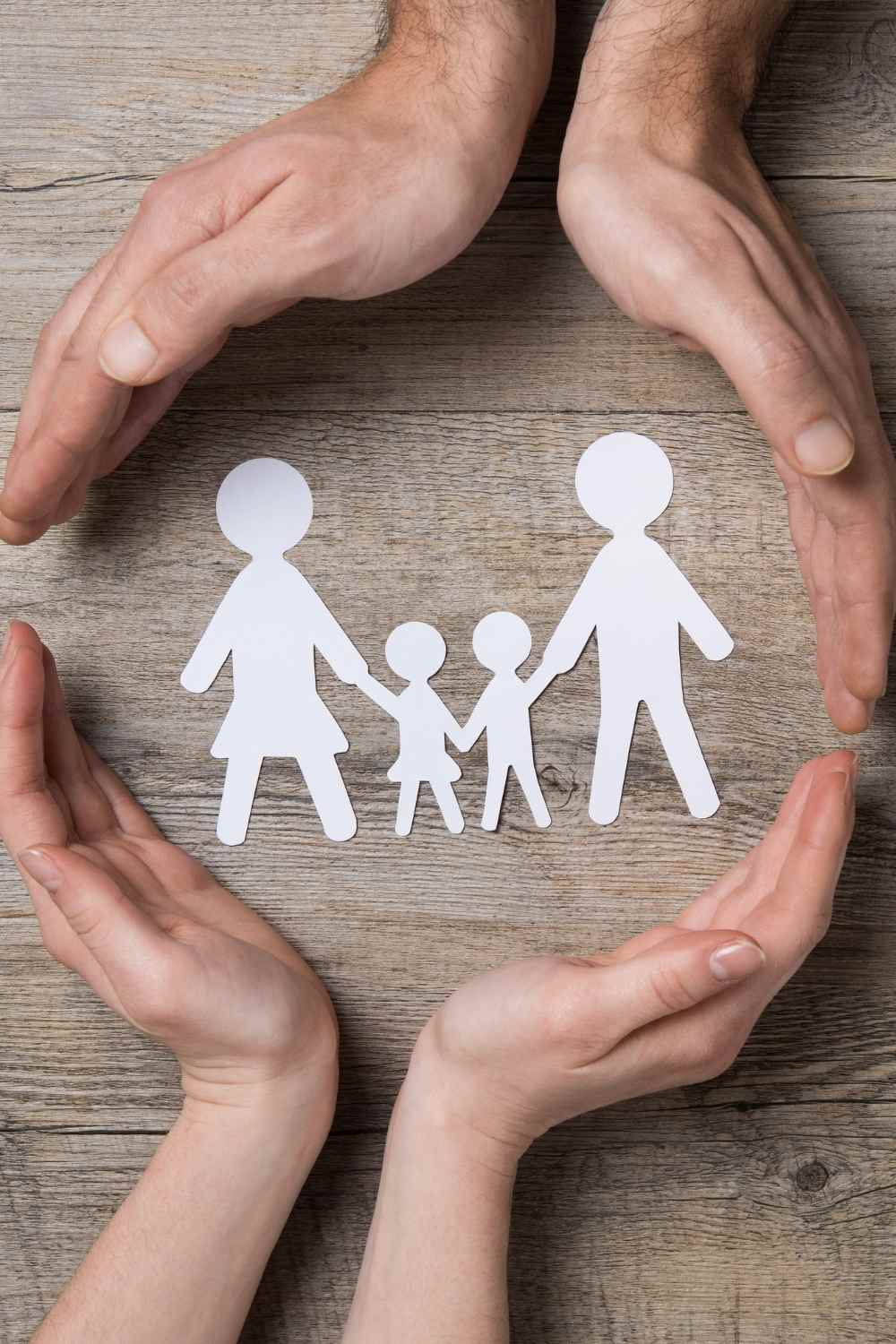 hands around paper cut outs of a family to show care