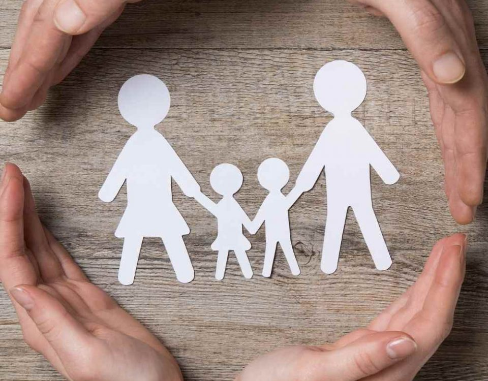 hands around paper cut outs of a working mum and her partner and children