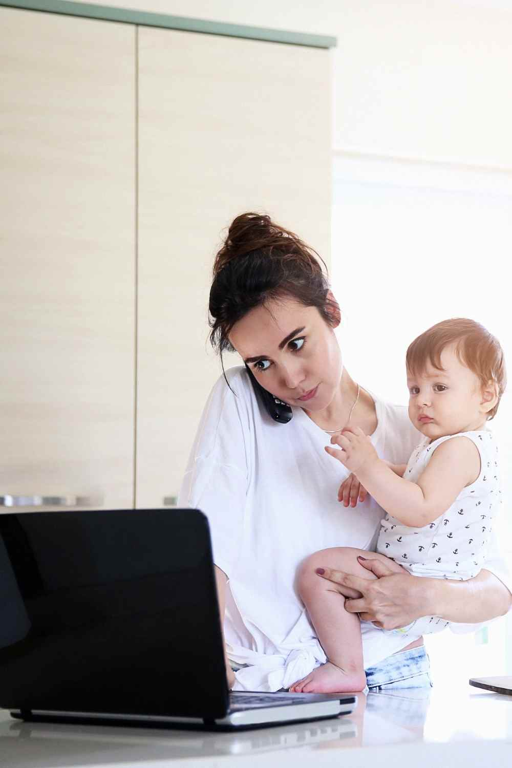 working mum holding a baby in the kitchen whilst on the phone and working on a laptop