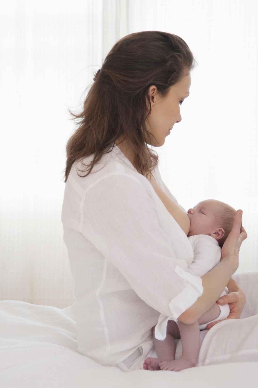 motherhood a woman feeding her baby