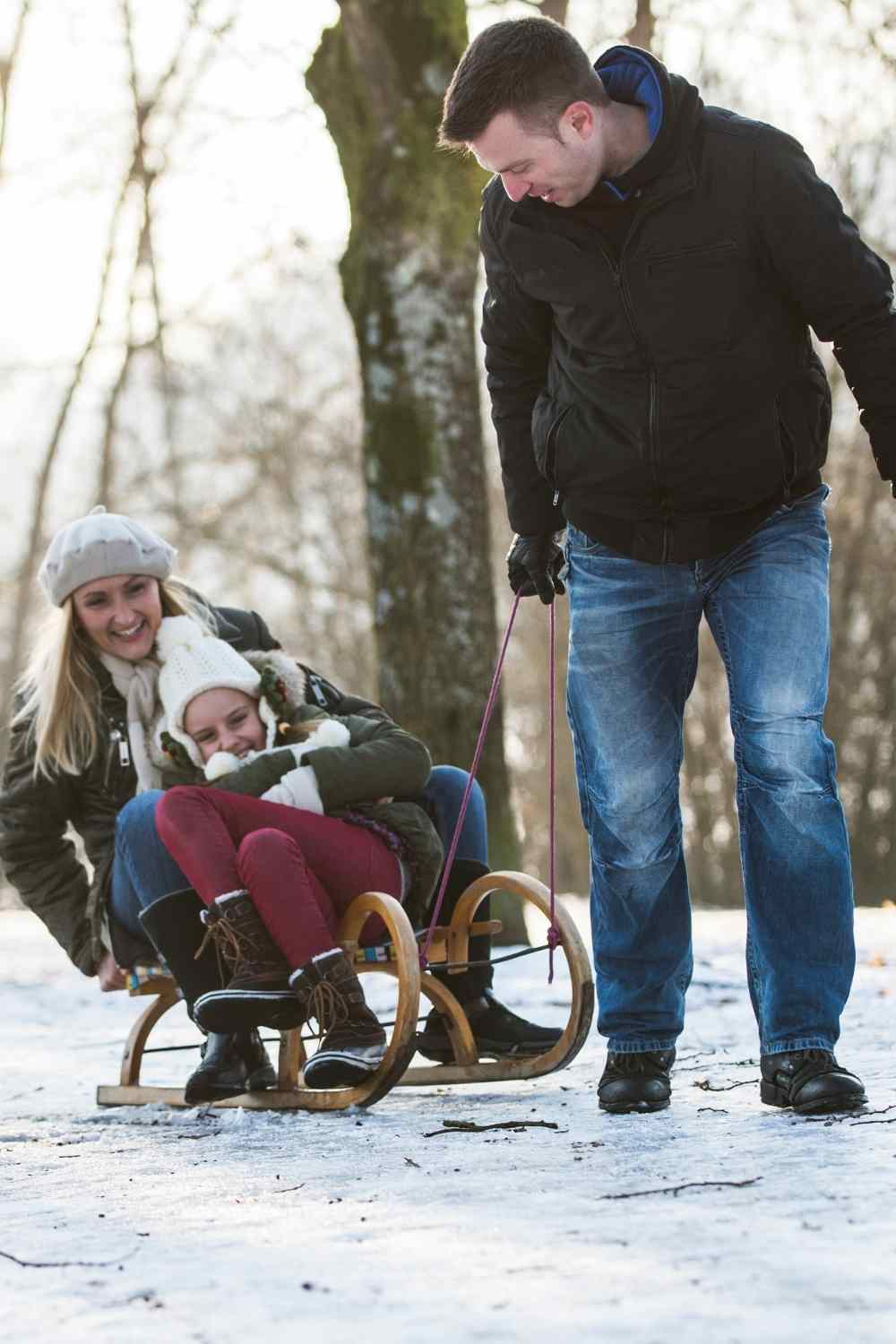 winter fun dad pulling family on a sled