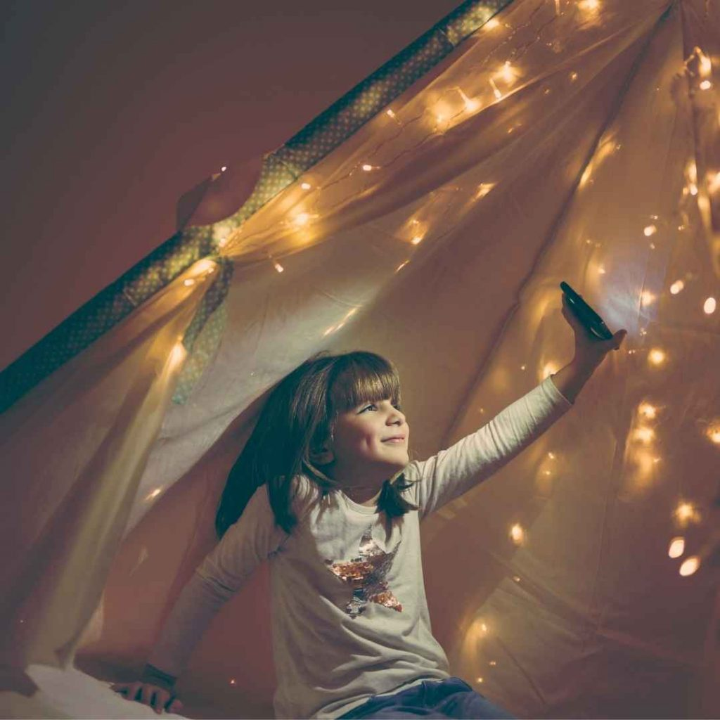 winter fun child in a teepee with twinkle lights