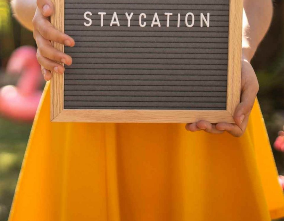 a sign that says staycation held by a woman