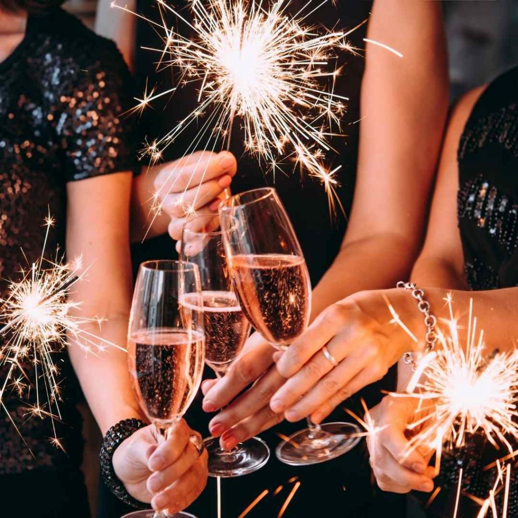 finding the perfect venue hands clinking glasses with sparklers