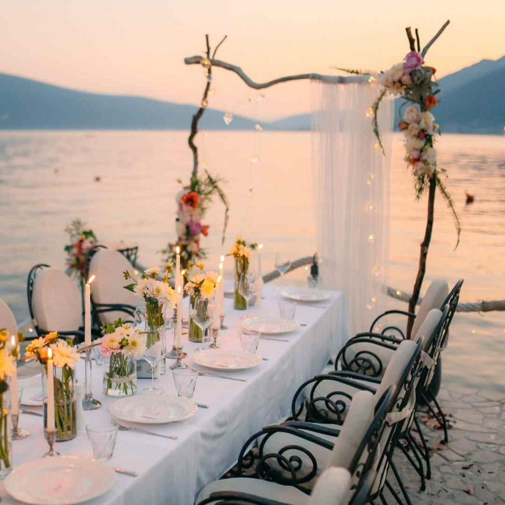 finding the perfect venue for a wedding - table and chairs and arch on beach at sunset