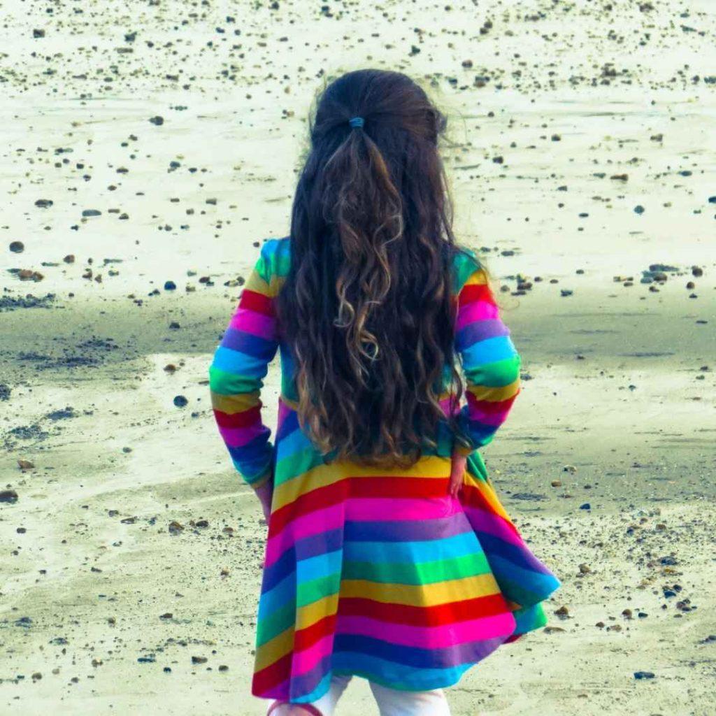 Alyssa on the beach in the childrensalon rainbow dress