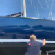 Yachtwrapping man applying stripes on yacht.