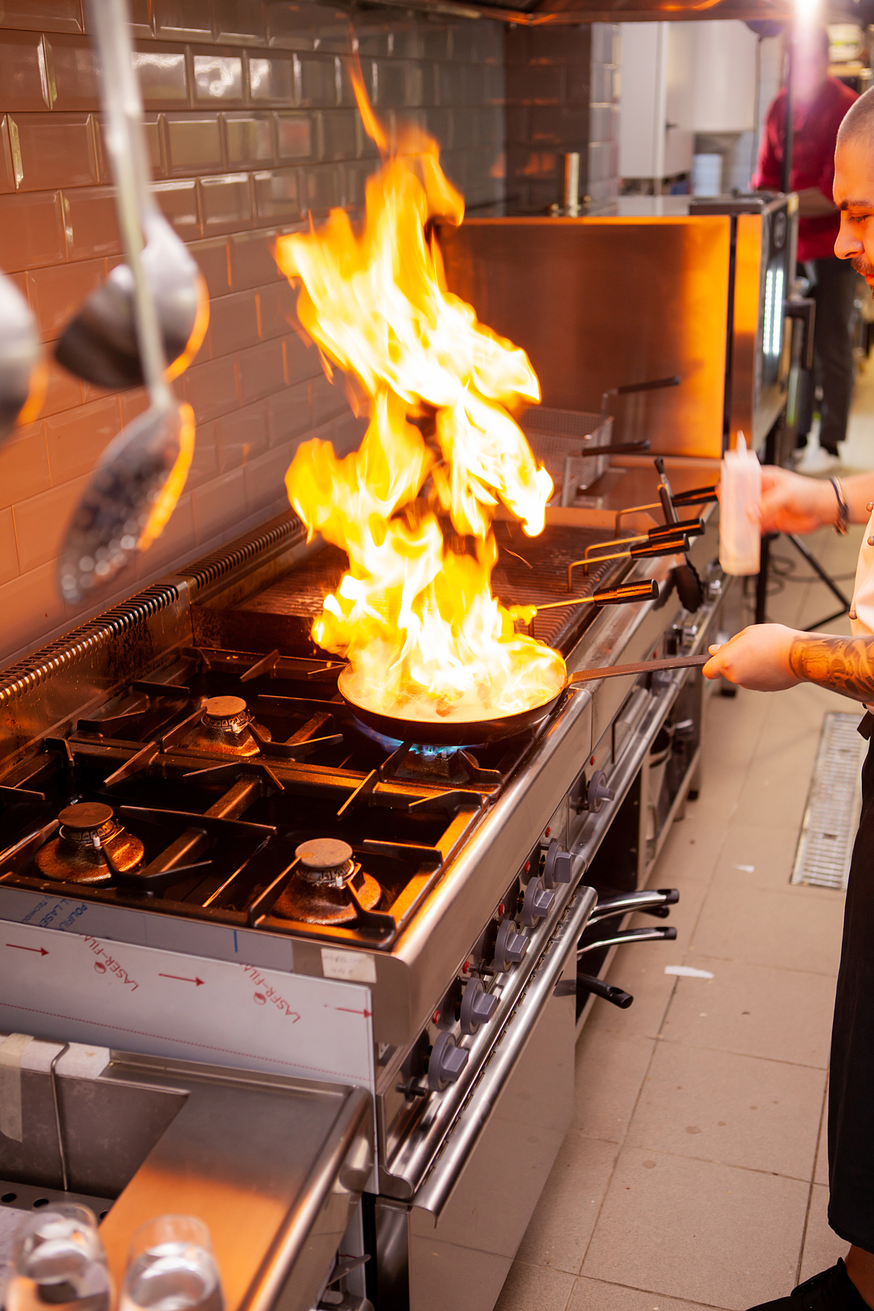 The chef prepares the dish on the stove with an open fire in the kitchen of the restaurant.