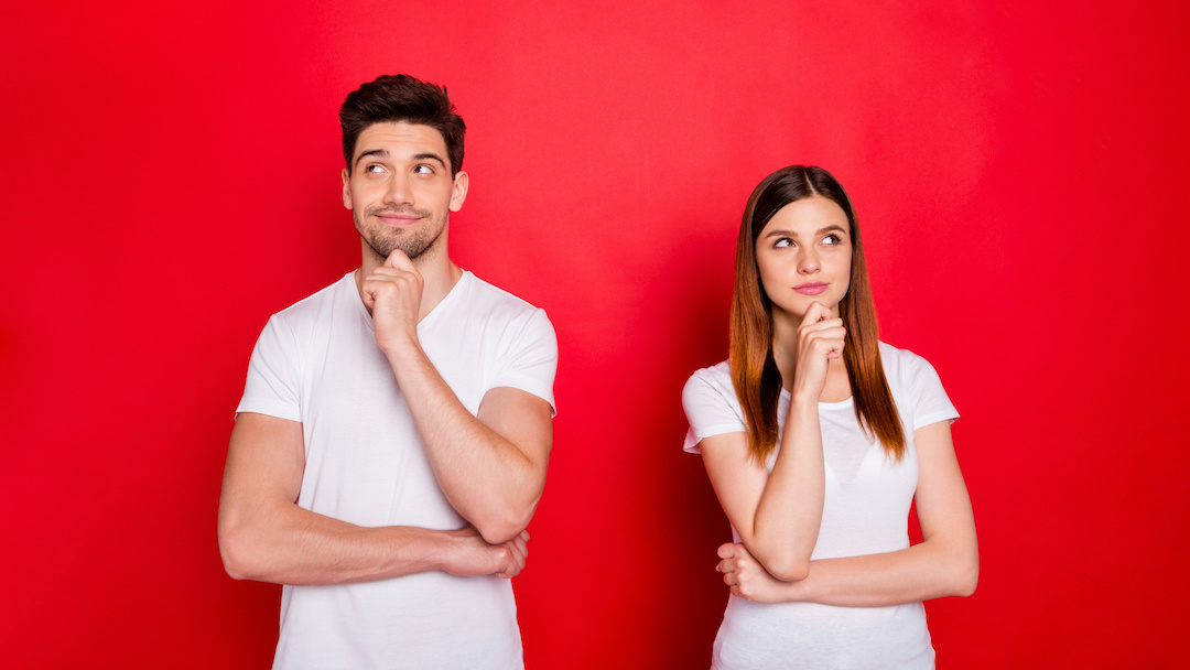 Young couple thinking against red background