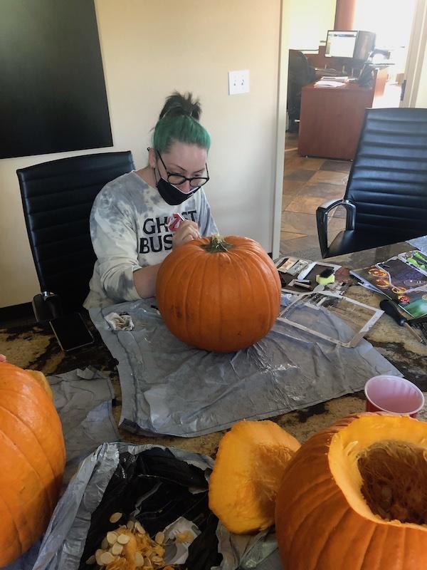 Caiti carves a pumpkin.