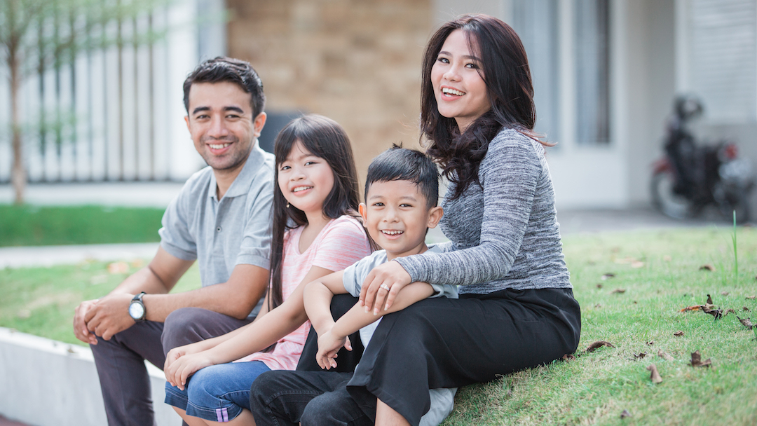 Happy young Asian family in front of home