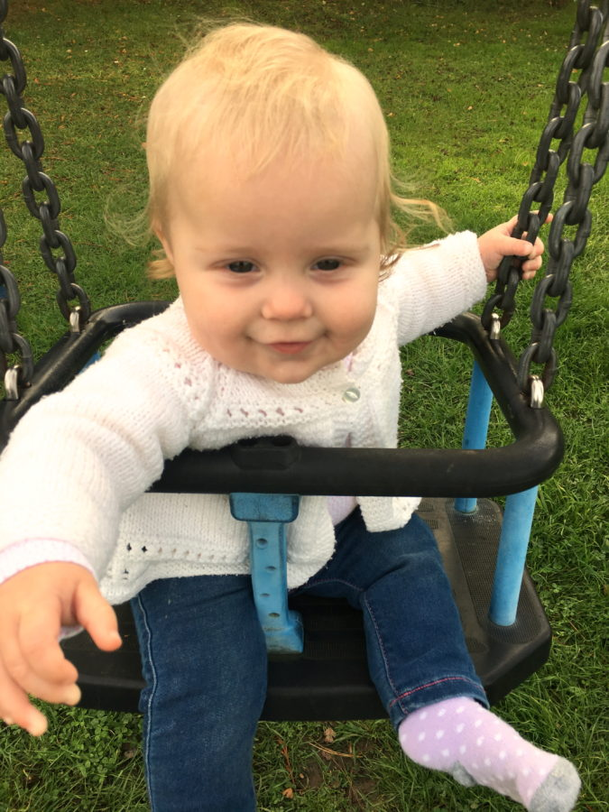 baby girl sitting on park swing, smiling