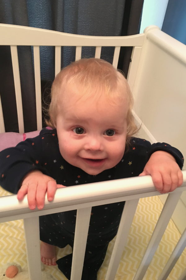 nine month old girl standing up in cot, in blue pyjamas, smiling