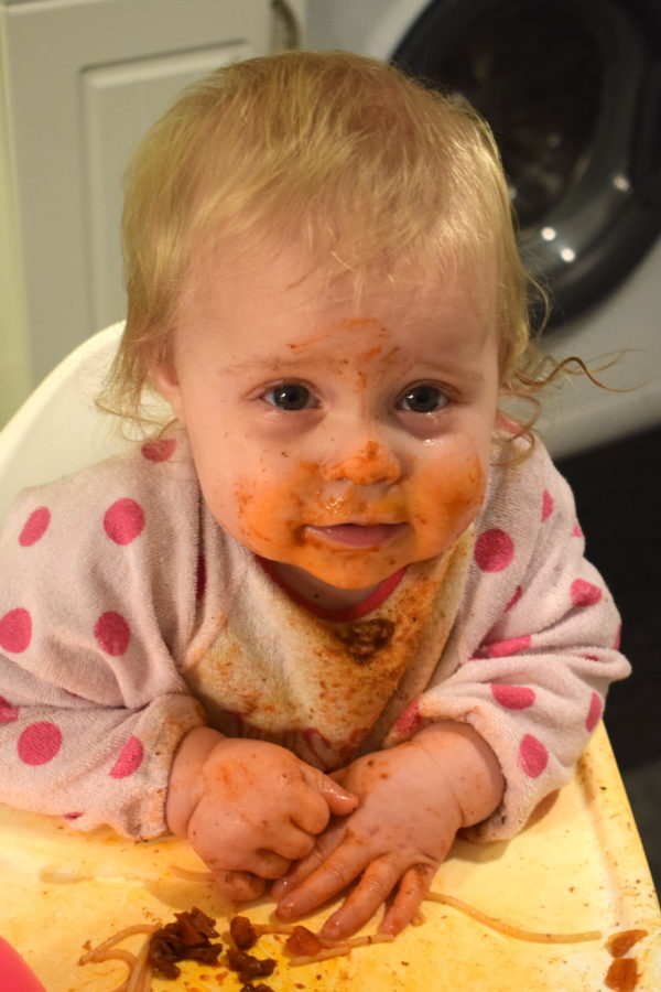 baby in highchair, covered in tomato sauce with spaghetti in front of her