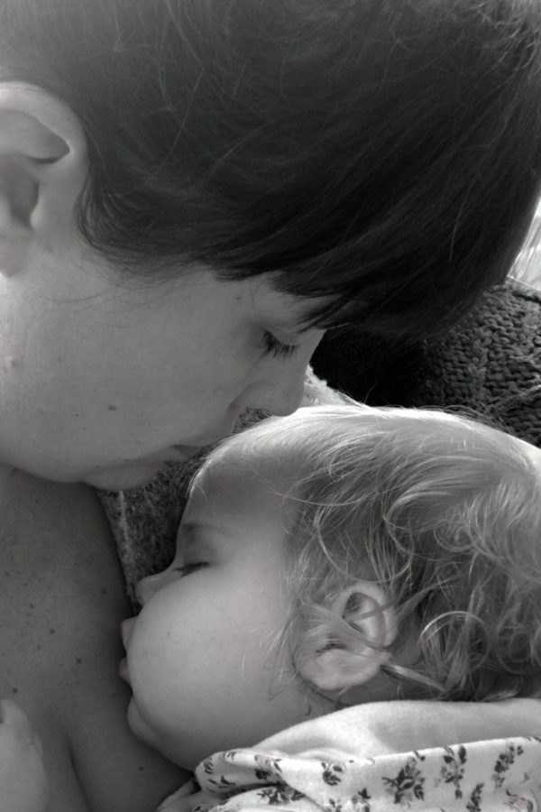 mother holding sleeping baby against her chest, kissing her head