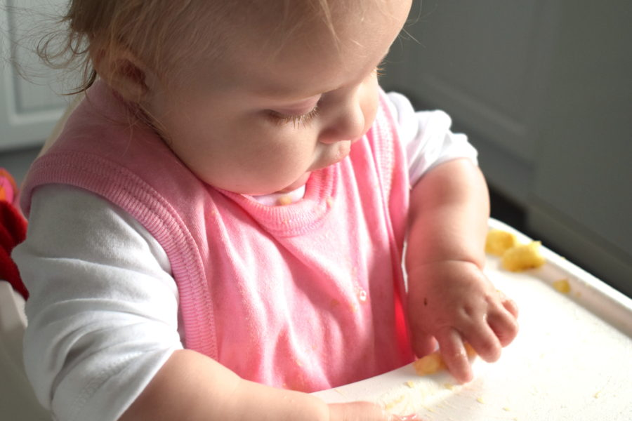 baby sitting in highchair, picking up a piece of banana, wearing pink bib