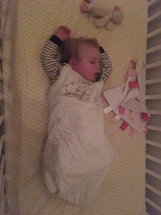 baby asleep in cot, lying on back with hands above head