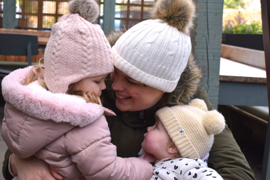 A mother holding two little girls, all looking at each other and smiling, each wearing a bobble hat and coat