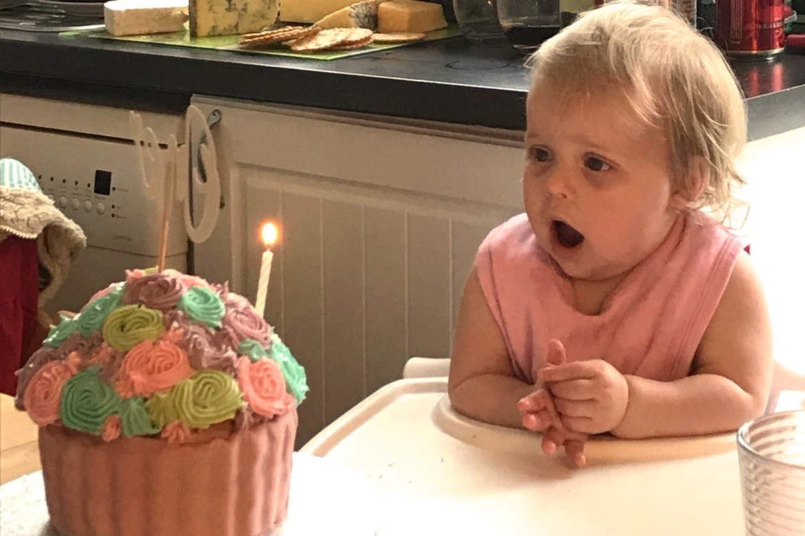 one year old looking at birthday cake in surprise