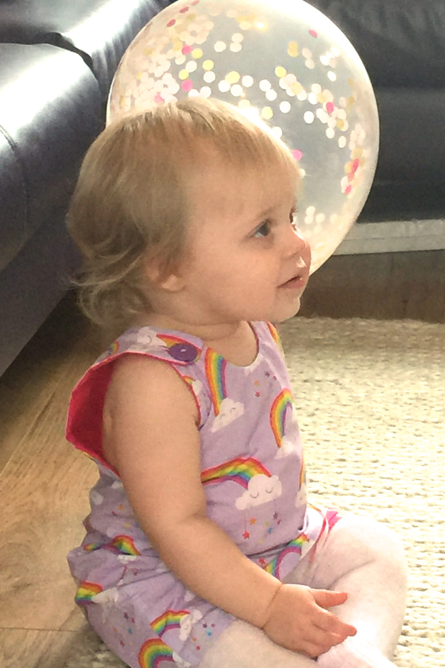 one year old in party dress sitting on the floor, holding a balloon
