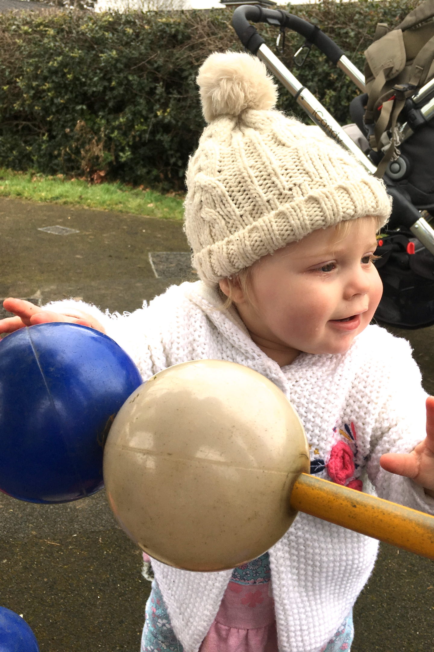 one year old girl in bobble hat, playing with oversized abacus