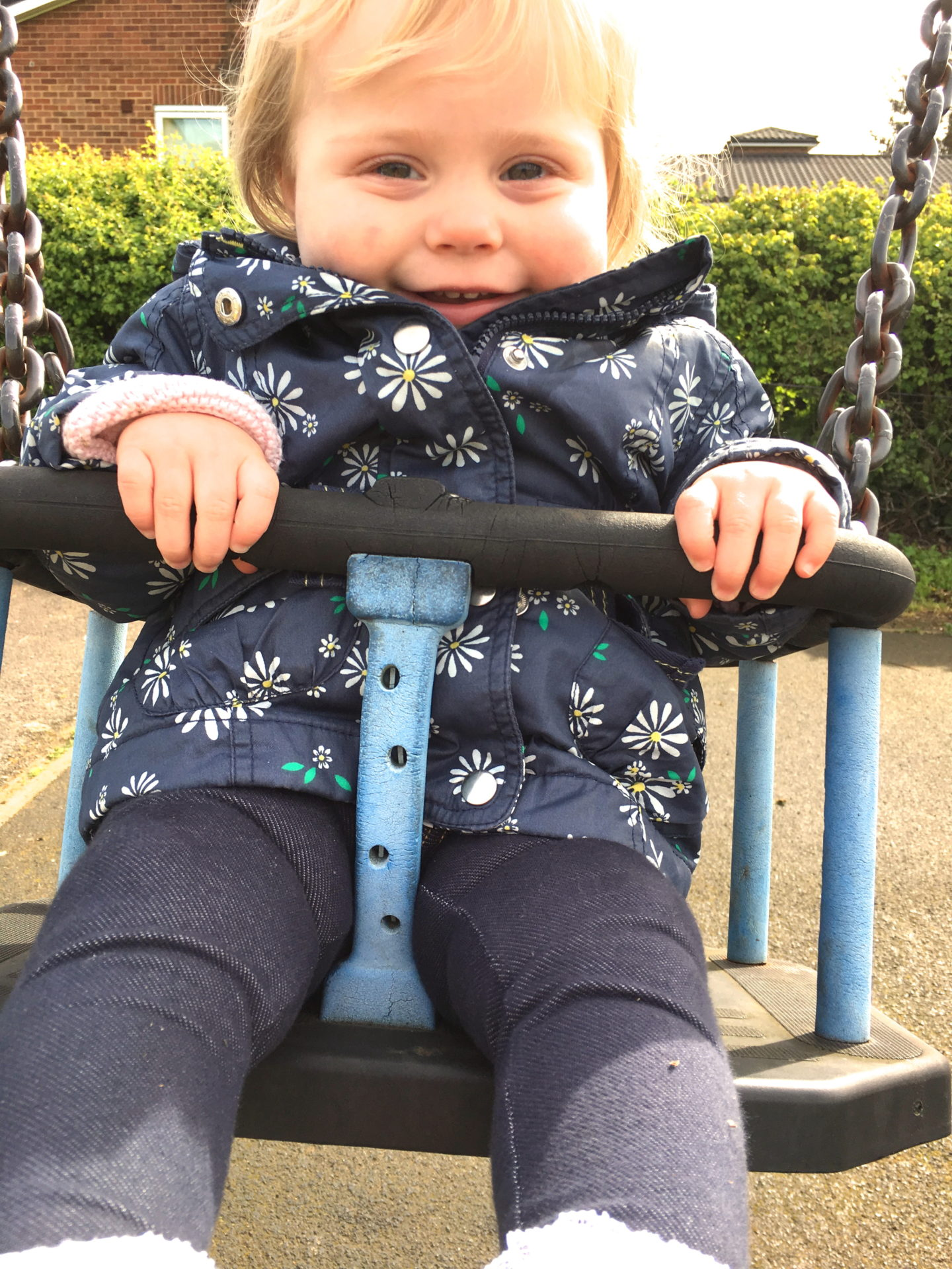 14 months old girl sitting in a swing