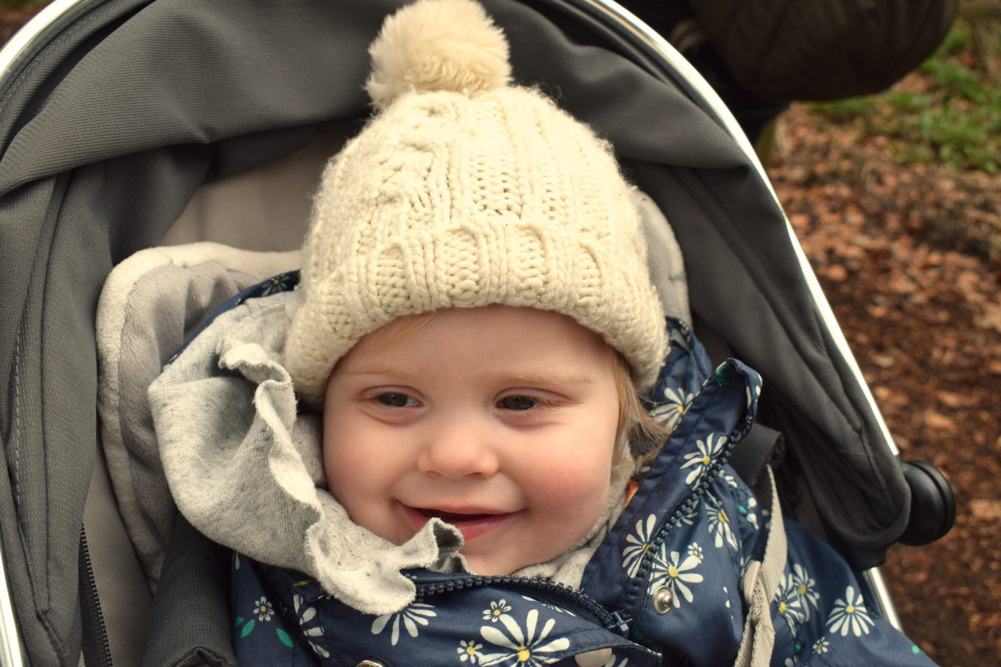 14 months old girl with bobble hat, sitting in pram, smiling