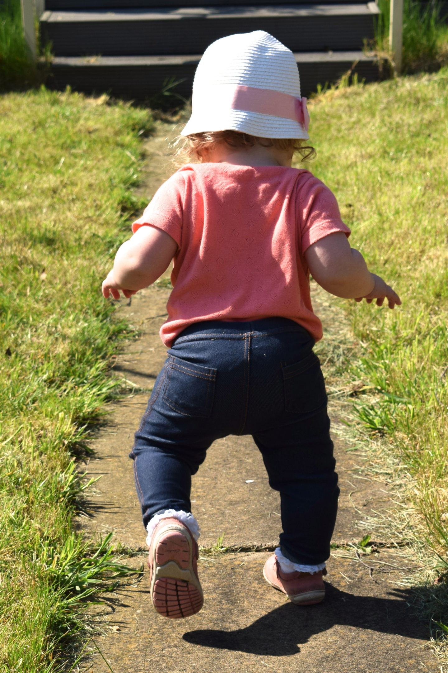 14 months old girl in sunhat, walking up the garden path, away from camera