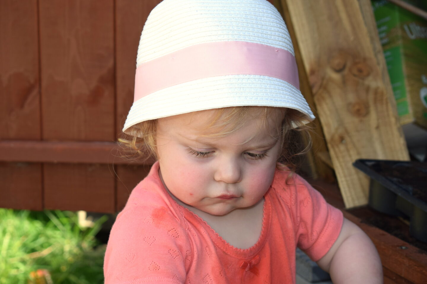 14 months old girl in sunhat, looking down