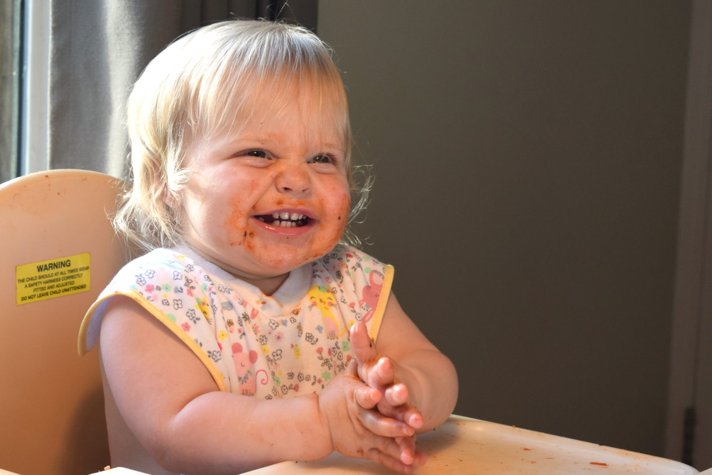 14 months old girl, sitting in highchair, laughing and clapping