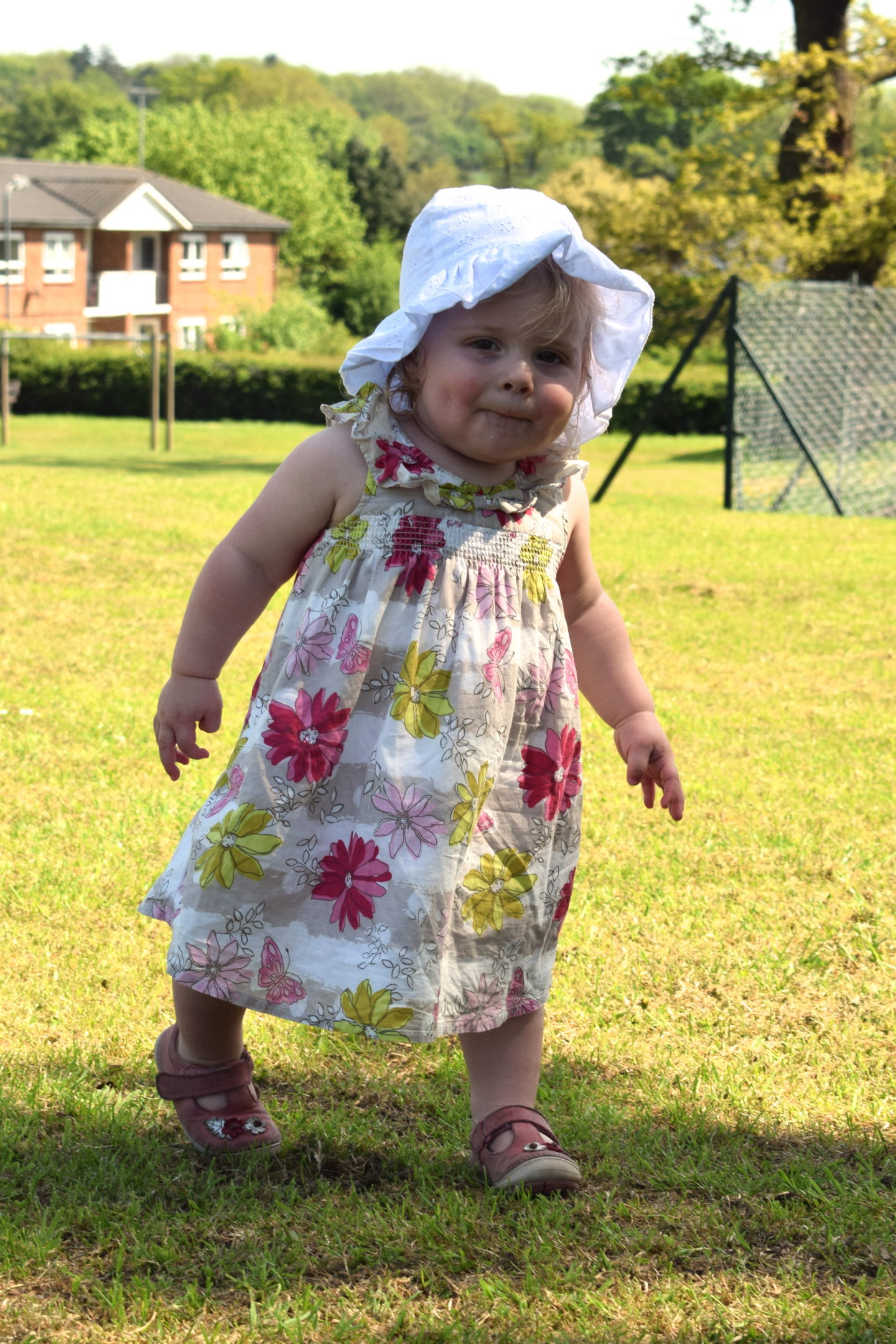 14 months old girl in sun dress and hat, in the park