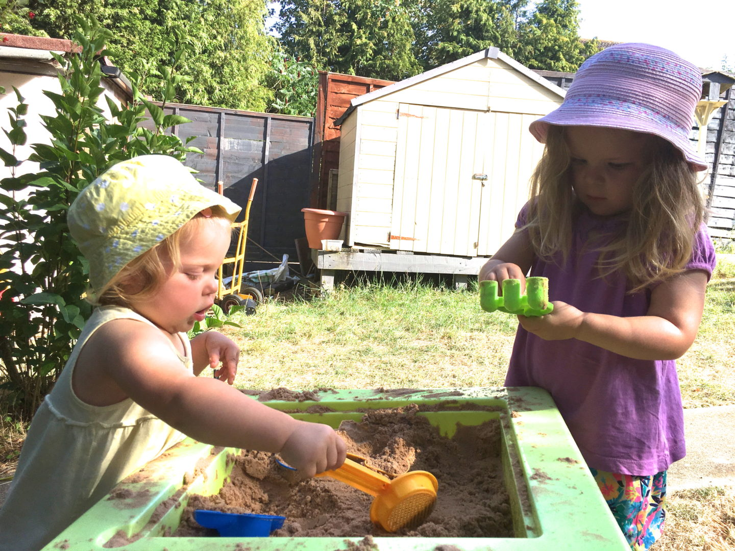 Two sisters playing side by side at a sand pit with sun hats on