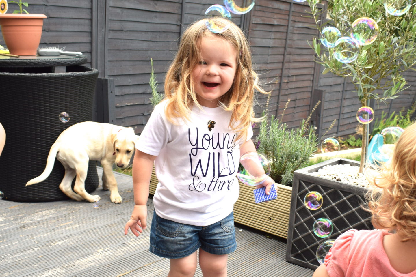 three year old laughing at bubbles in the garden