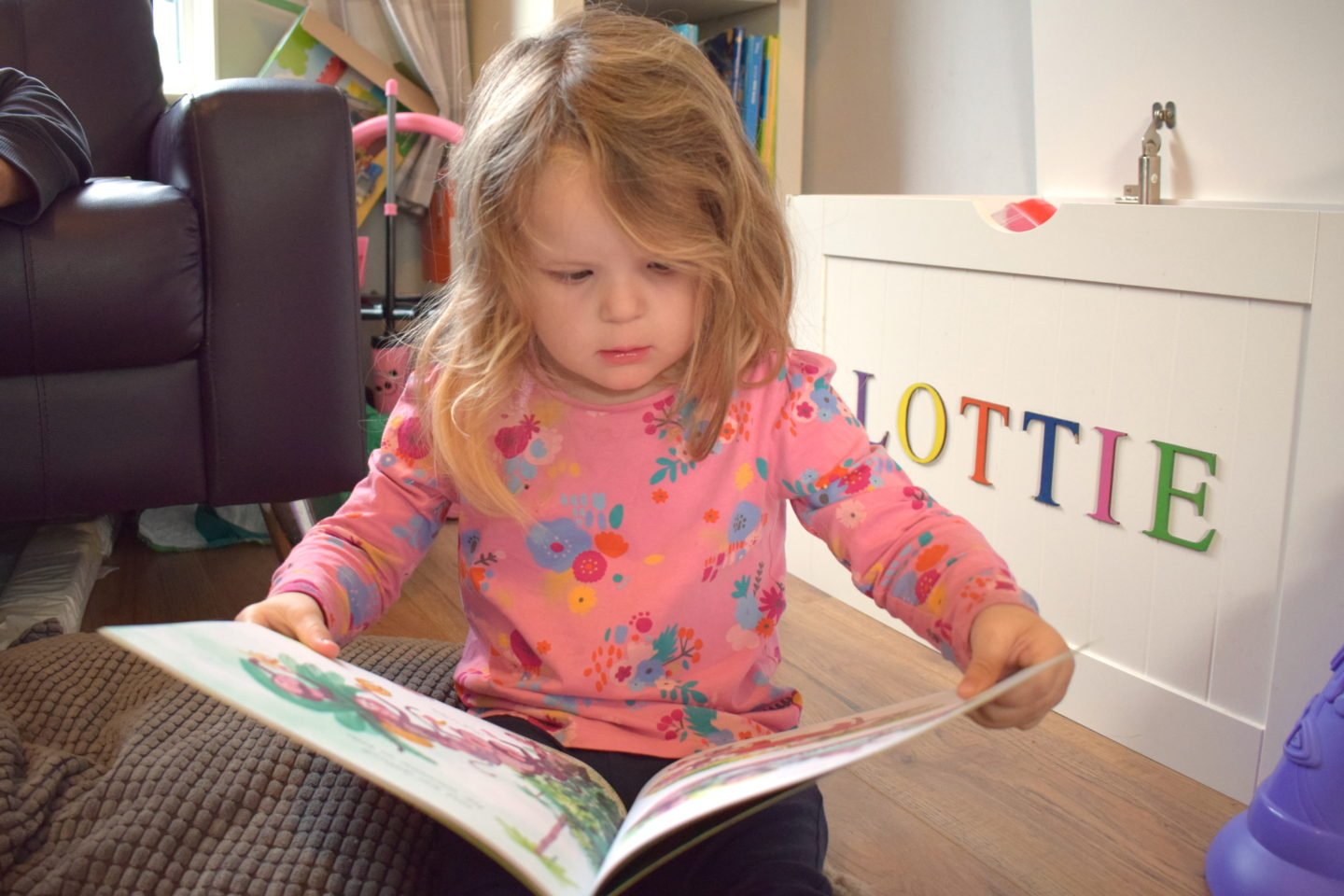 three year old sitting on the floor reading a book - time to read