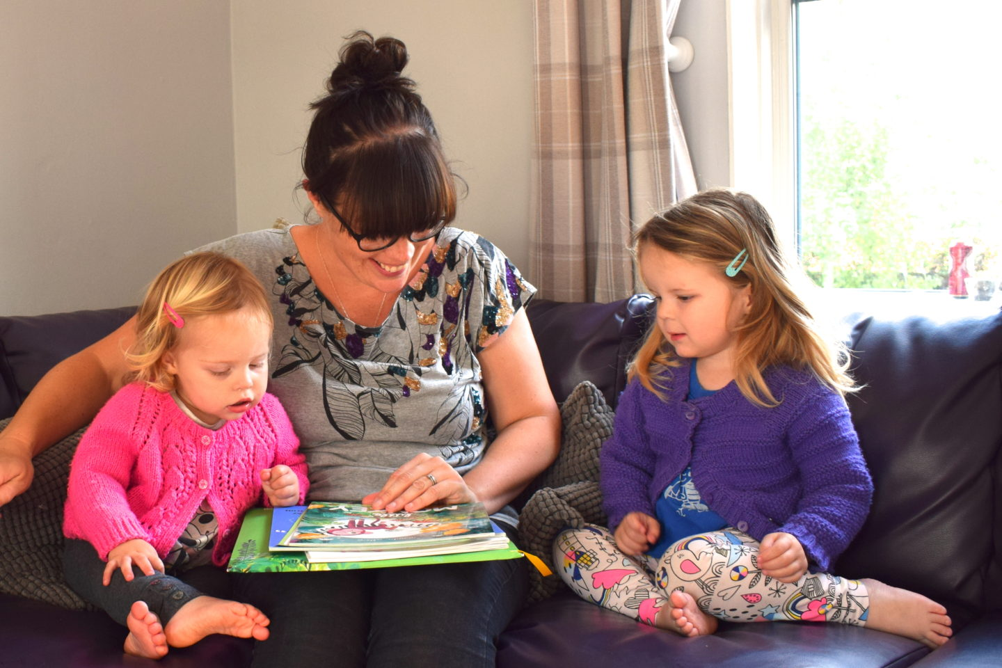 mother making time to read with preschool girls