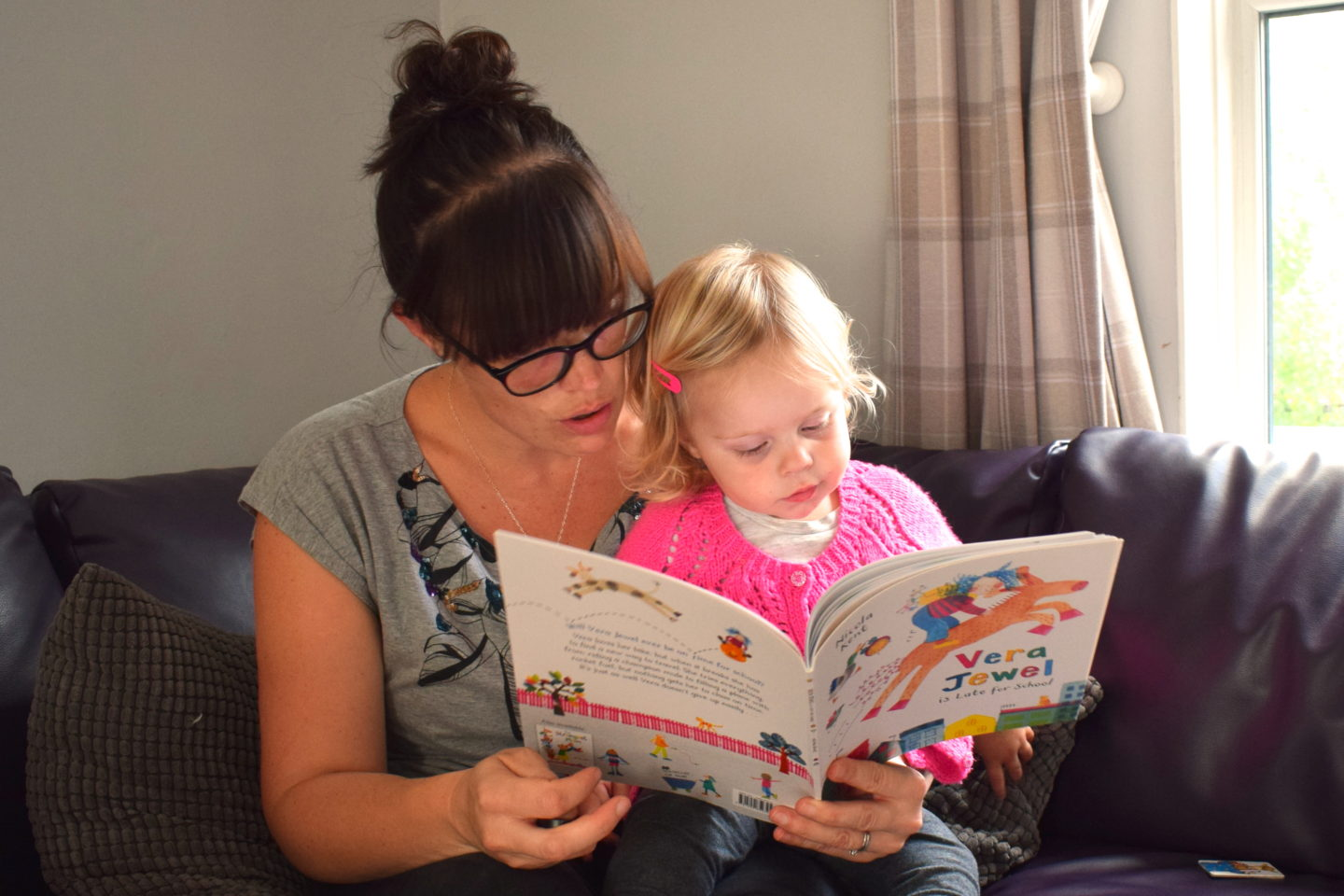 mother making time to read with one year old on her lap