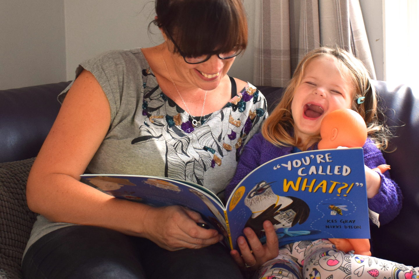three year old laughing at a story during time to read with mother