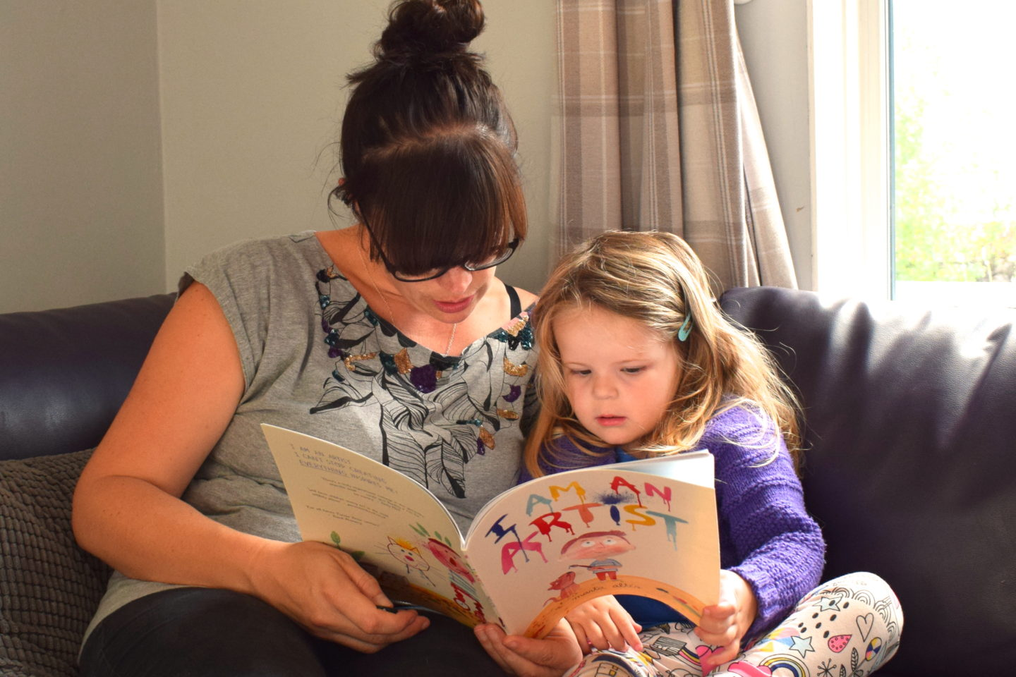mother making time to read with three year old