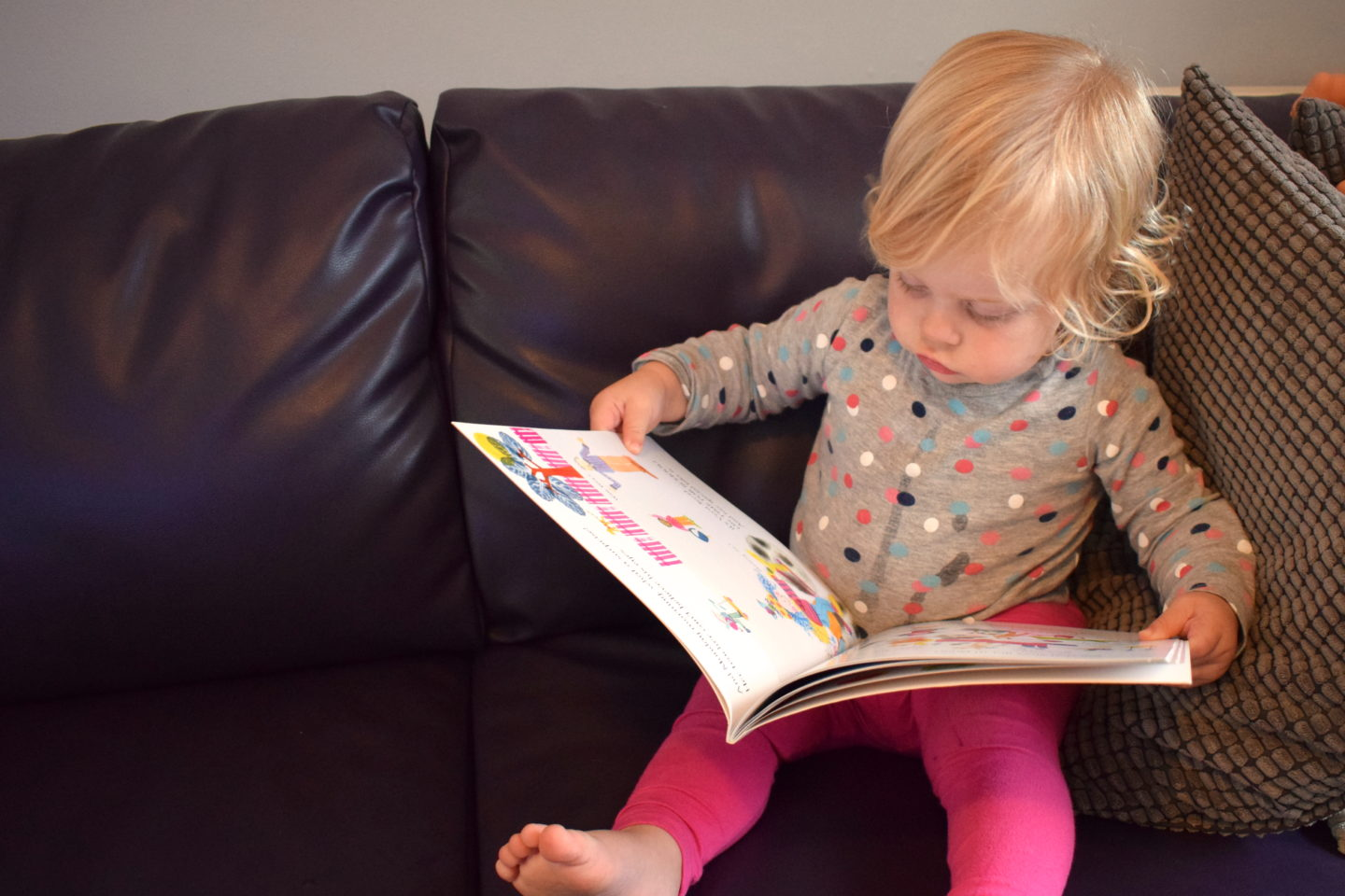18 month old girl reading a book on the sofa - time to read