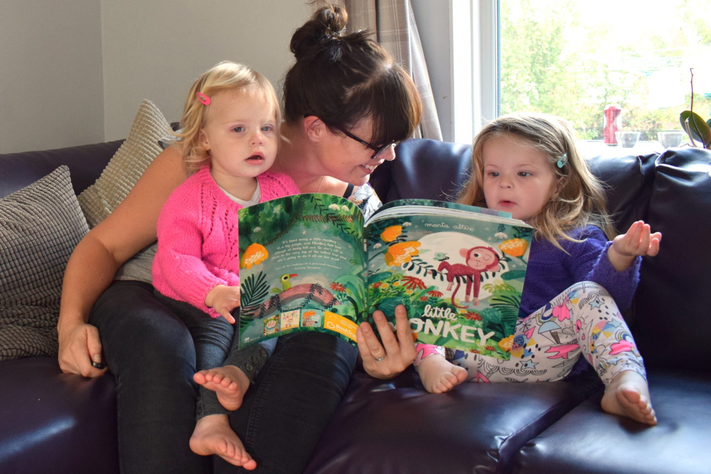 Mother sitting with two preschoolers reading - time to read