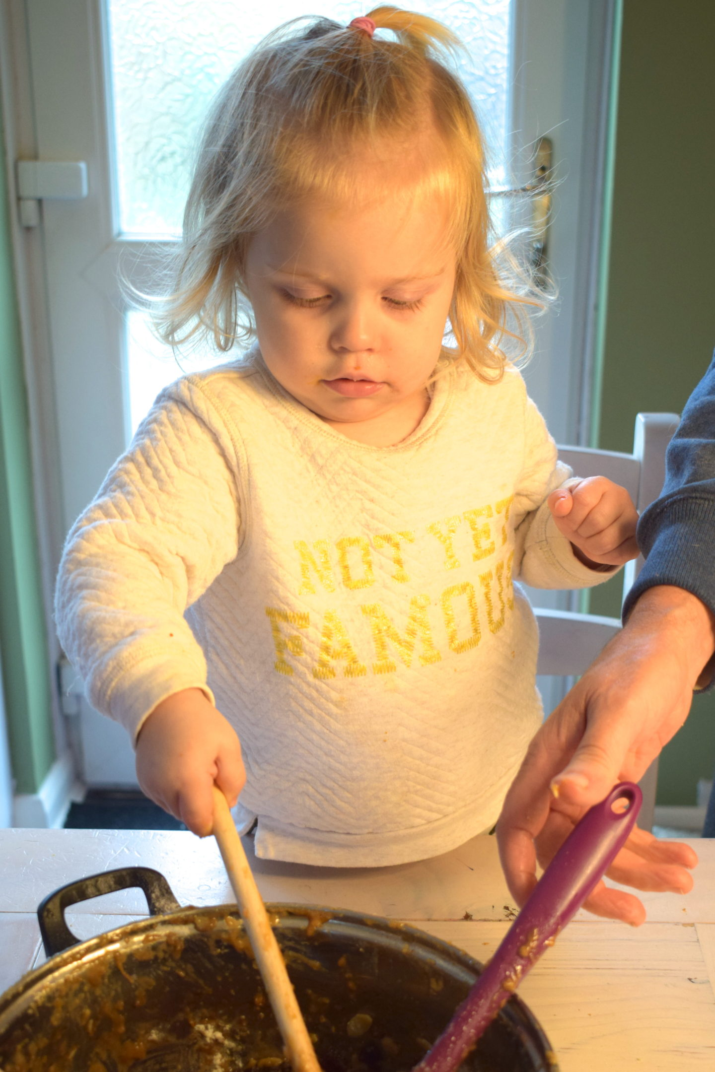 22 month old girl standing at table stirring cake mixture