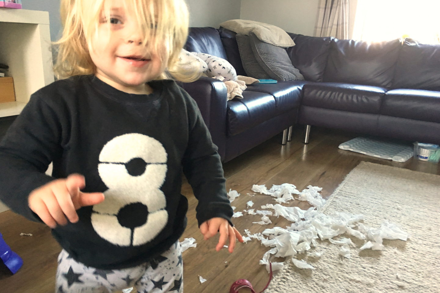 22 months old girl with box of tissues tipped up on the floor