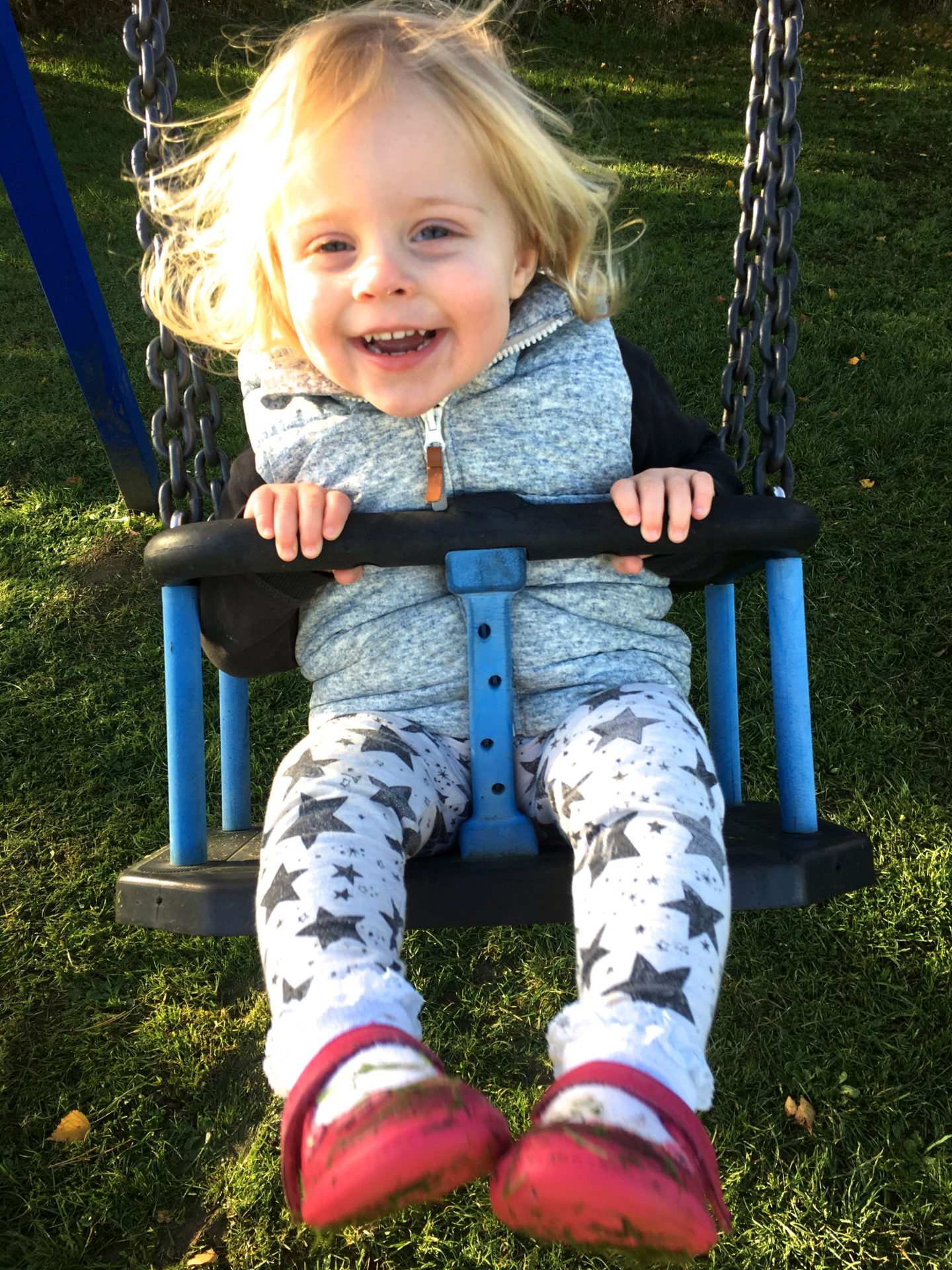 22 months old girl on a swing, smiling