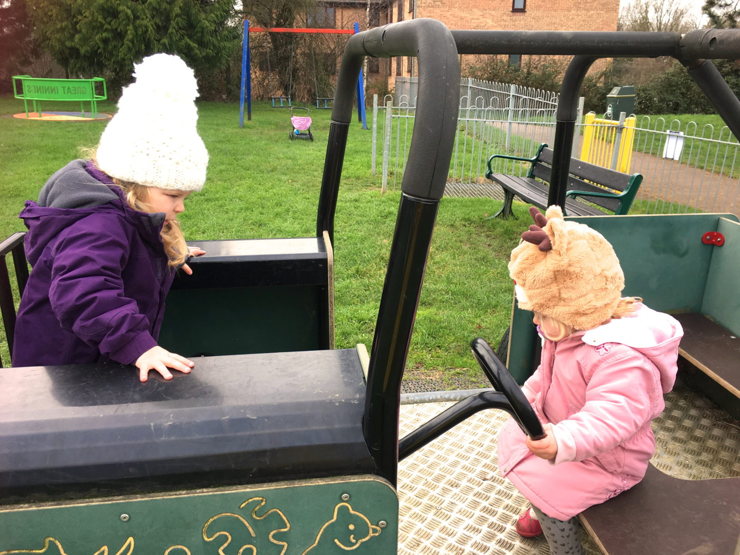 Two toddler sisters playing on a climbing frame car in a playground