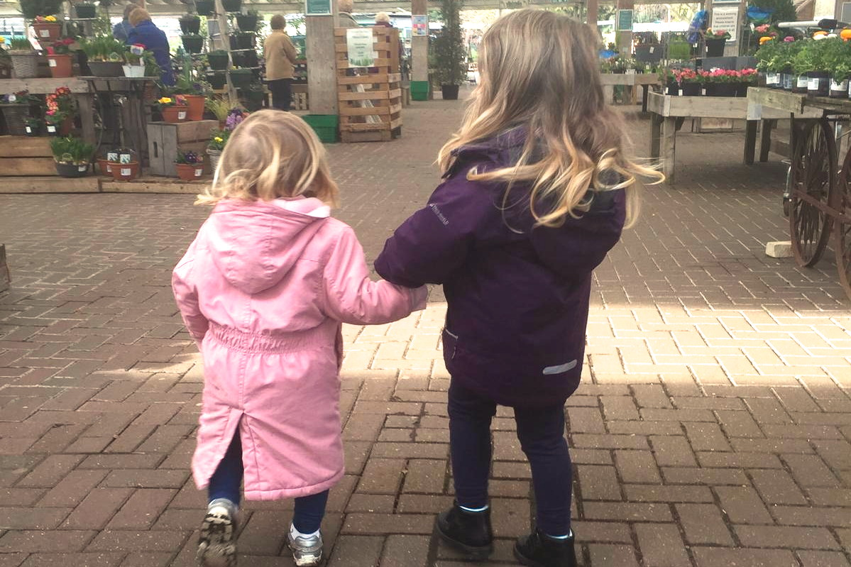 two toddler sisters walking through a garden centre holding hands