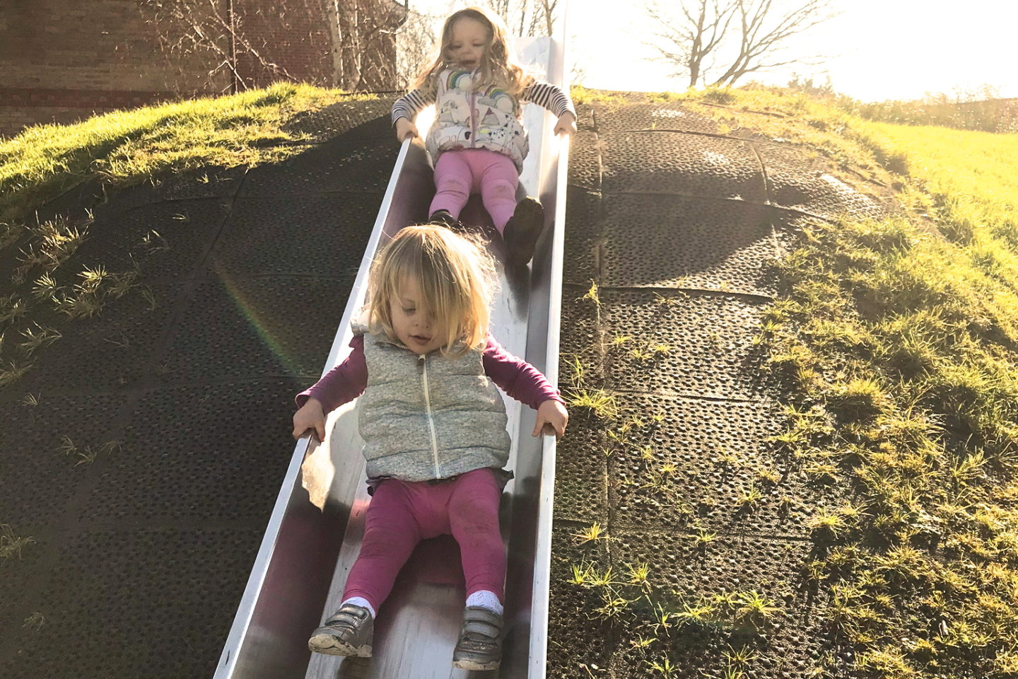 Two sisters going down a slide behind one another