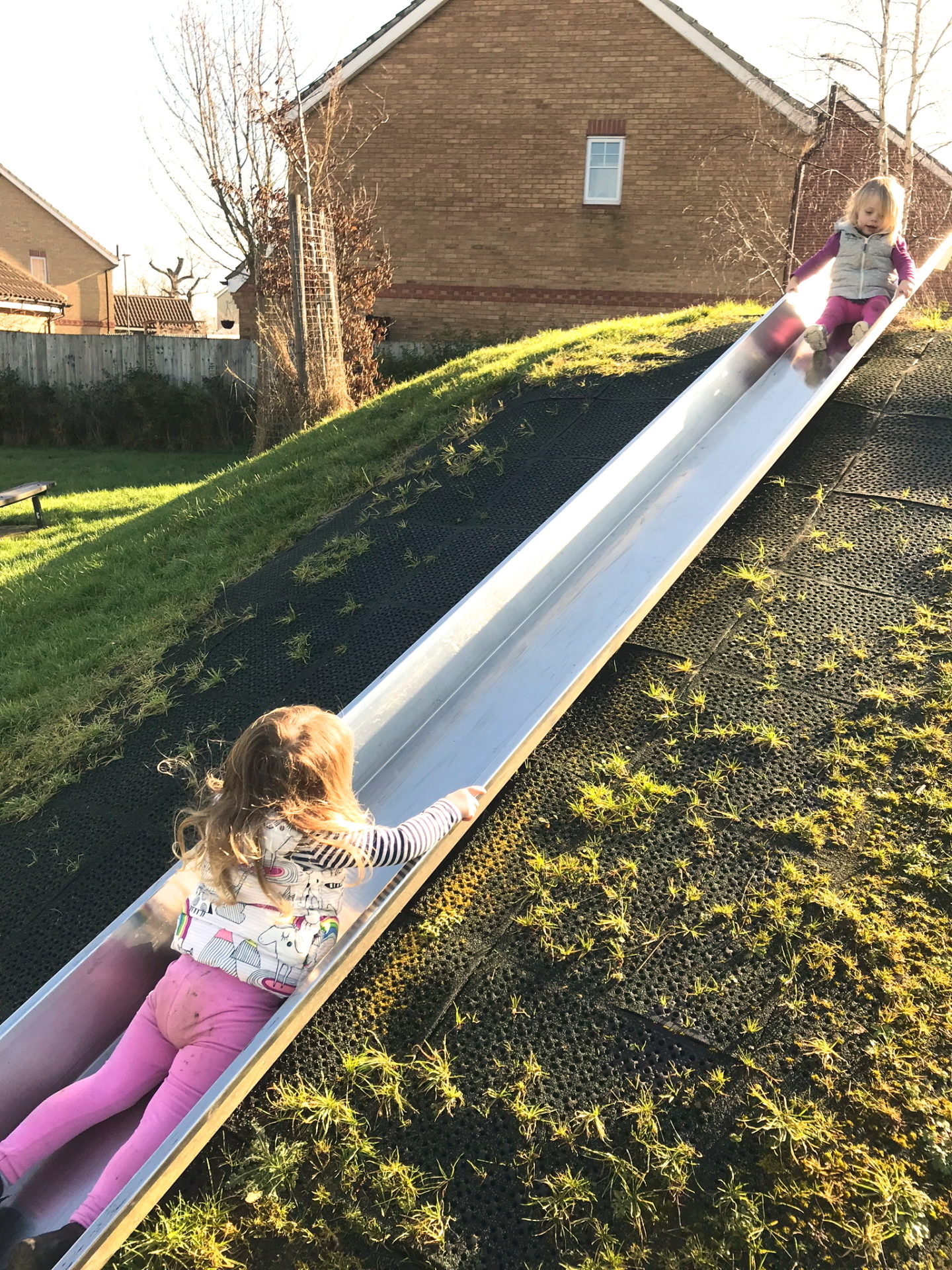 two sisters playing on a slide