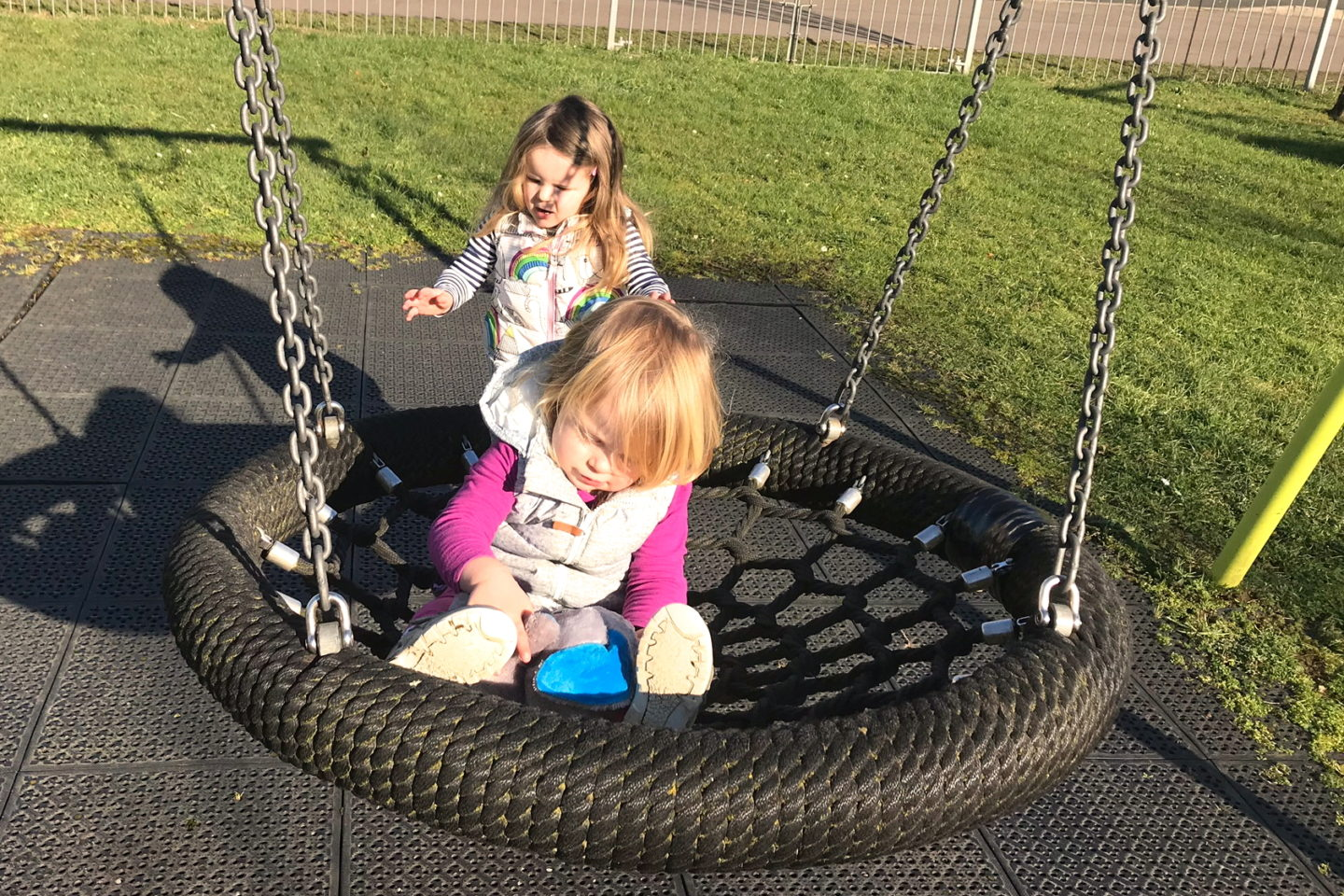toddler sitting on a net swing with big sister pushing her
